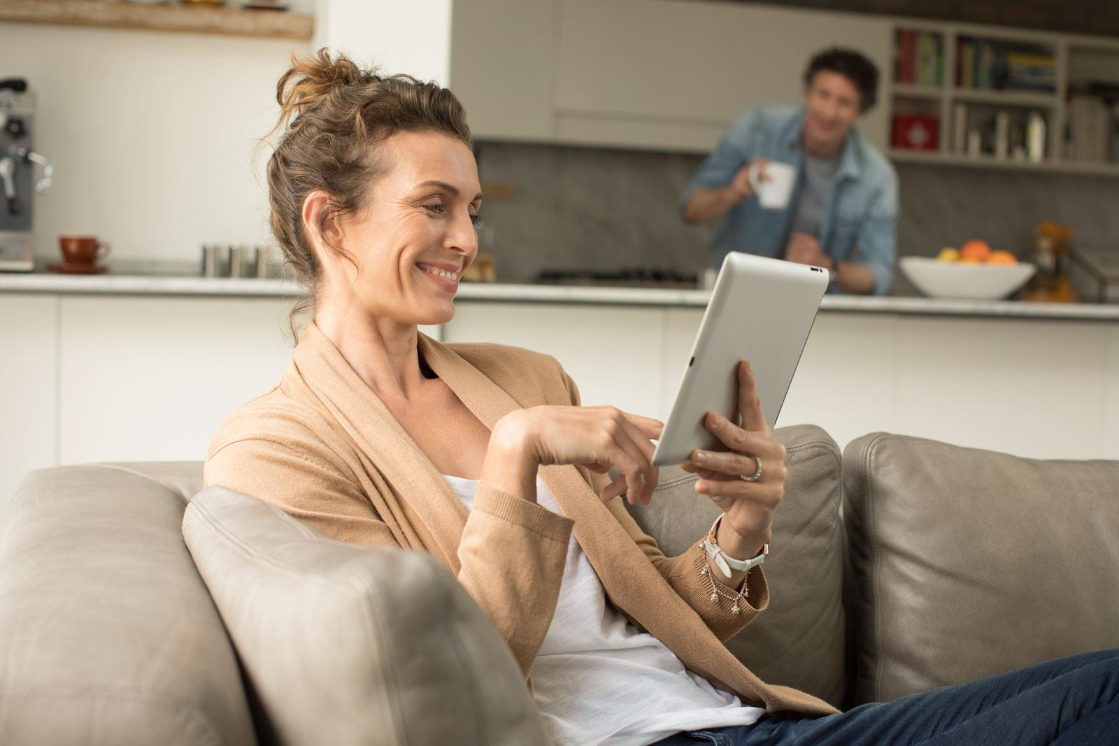 woman-sitting-on-couch-with-tablet