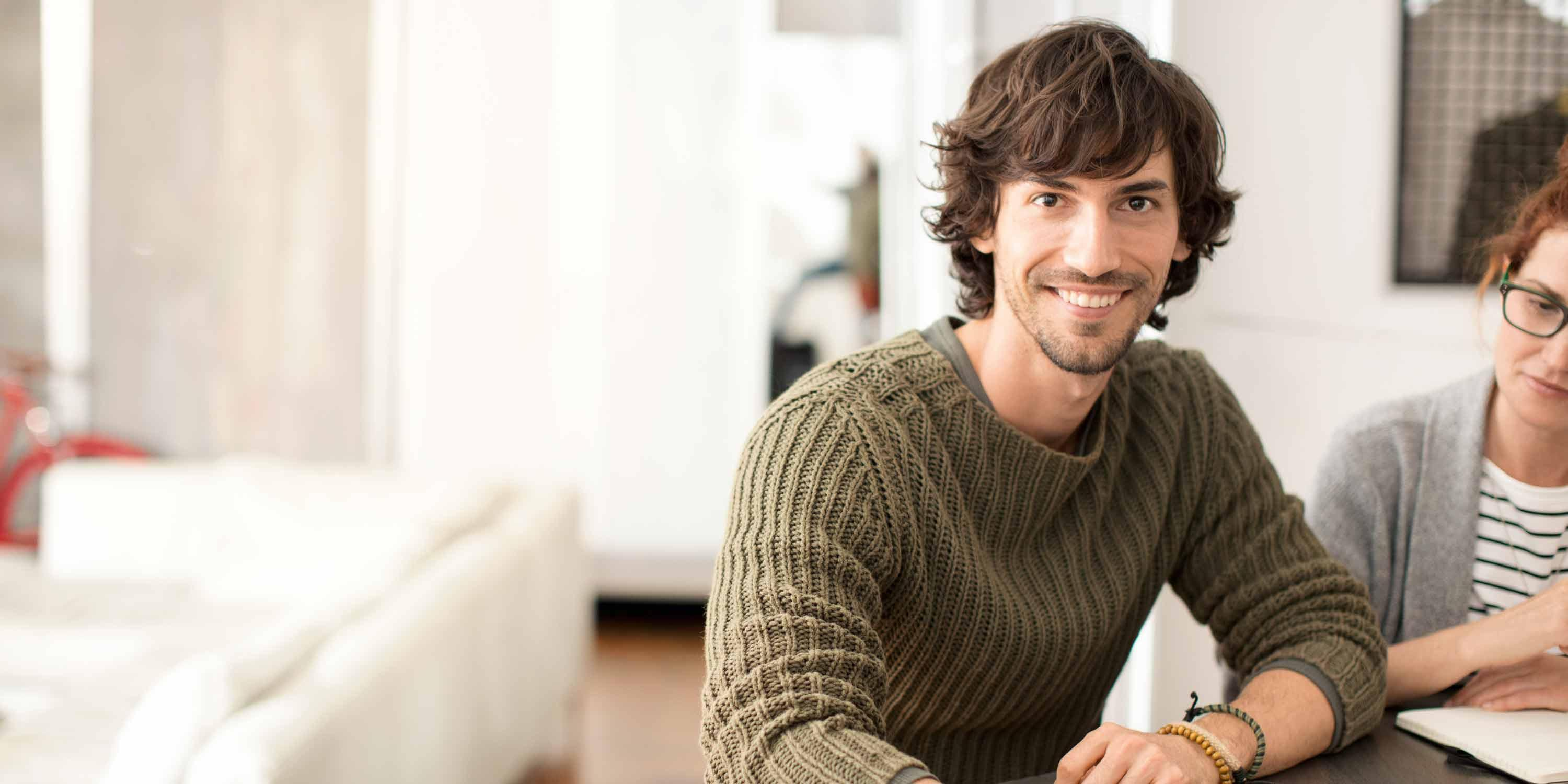 young-man-sitting-on-sofa-smiling